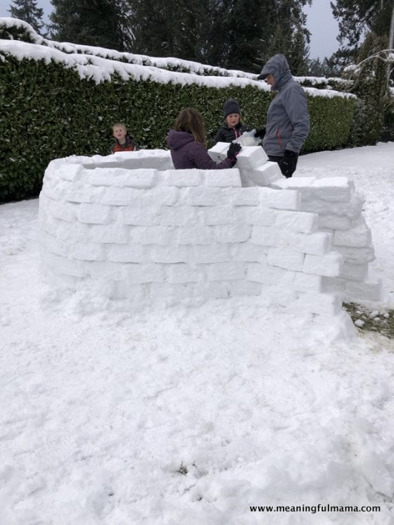 kids building an igloo with their dad