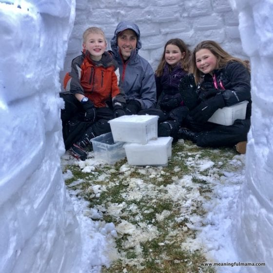kids inside an igloo they built with their dad
