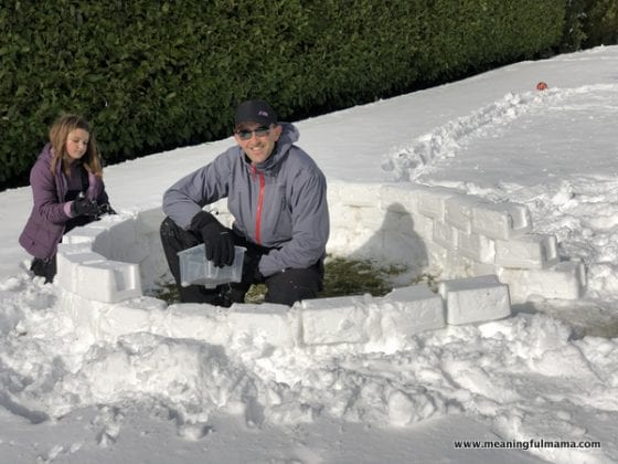 man building an igloo with daughter
