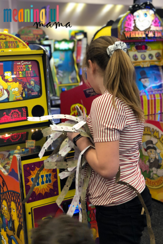 Girl Playing Video Game at Chuck E. Cheese's with Tickets in Hand - Staycation ideas for kids