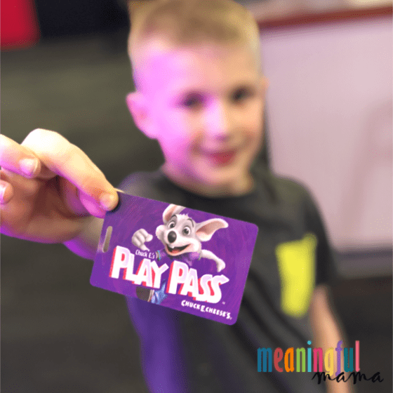 Boy holding Chuck E. Cheese's Play Pass Card while enjoying a staycation idea