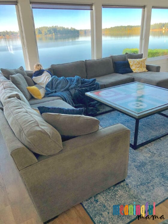 Girl Laying on couch staring out the window at the lake on washable rug