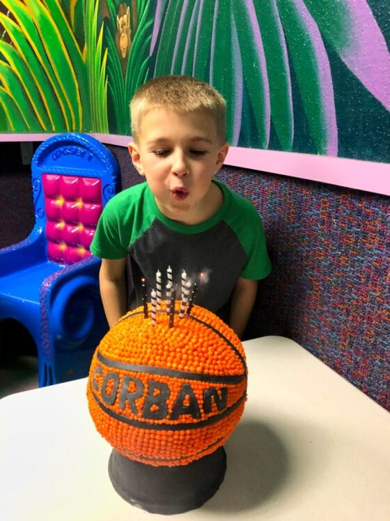 boy blowing out candles on sphere basketball cake