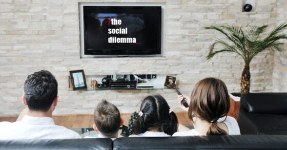 Family watching TV with a Parent's review of the Social Dilemma on Facebook